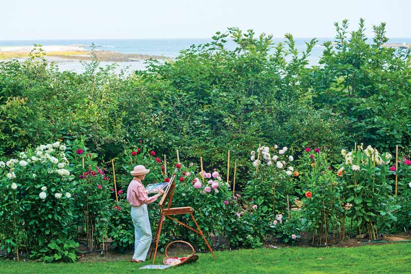 Artist Sus Miller paints in her garden by the sea