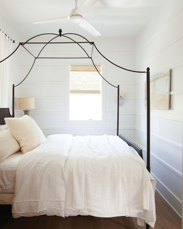White bedrrom with black iron canopy bed