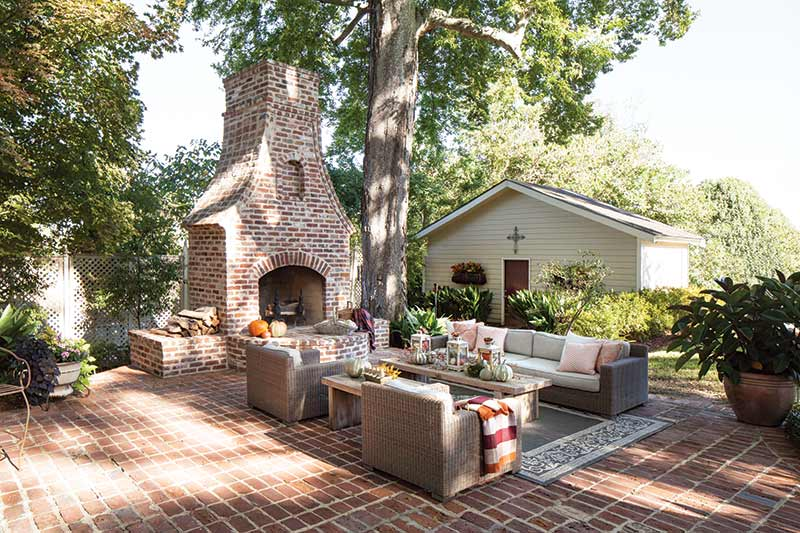 outdoor living space with brick fireplace