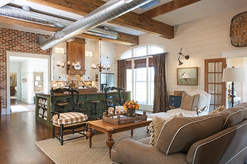 open-concept living area and kitchen with exposed brick and shiplap.