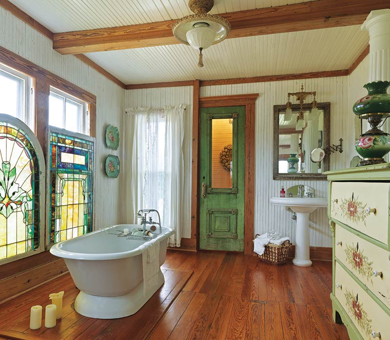 bathroom with green antique door and stained glass