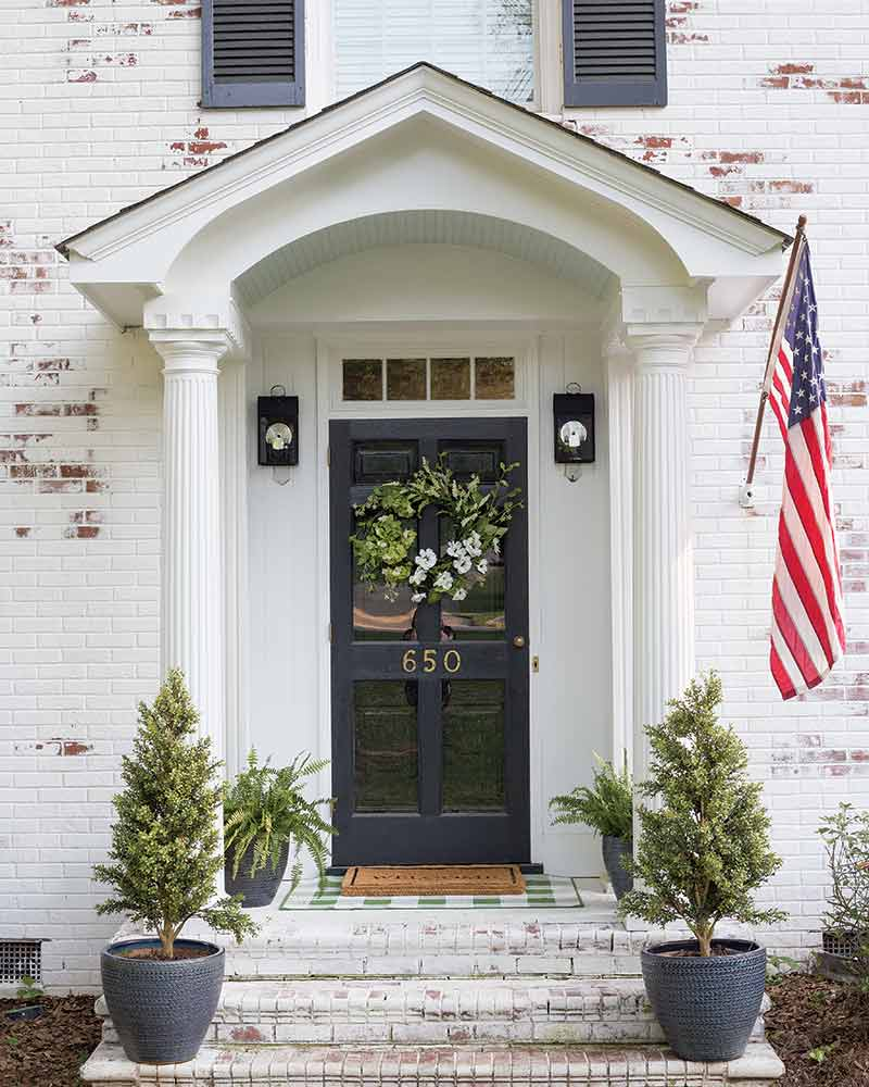 limewashed brick home with dark gray front door