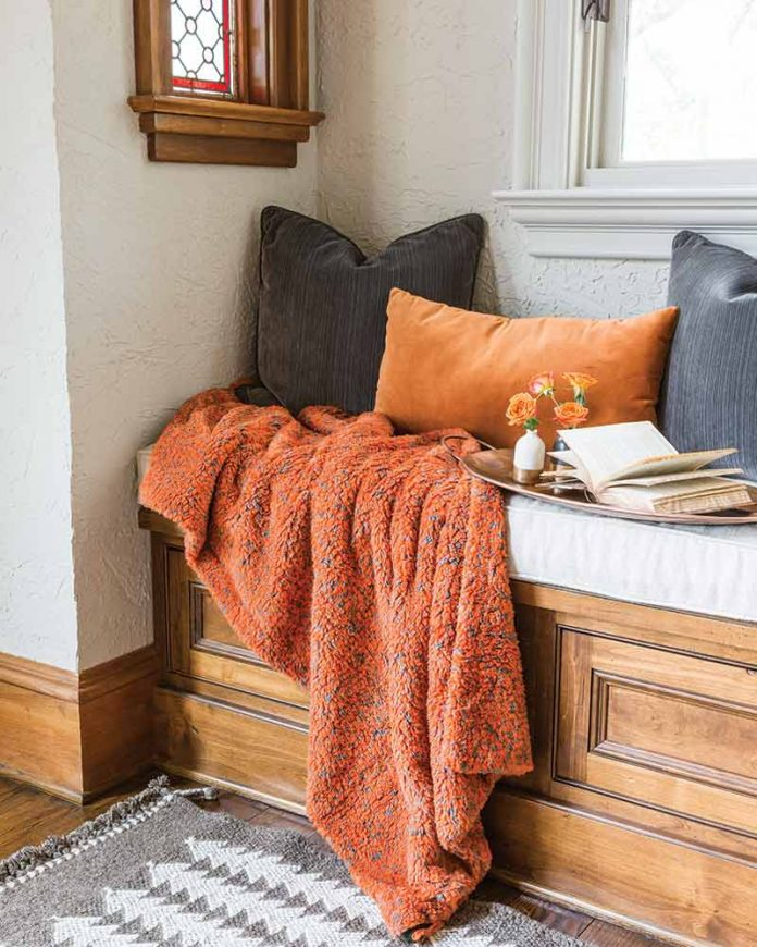 orange throw blanket and throw pillows