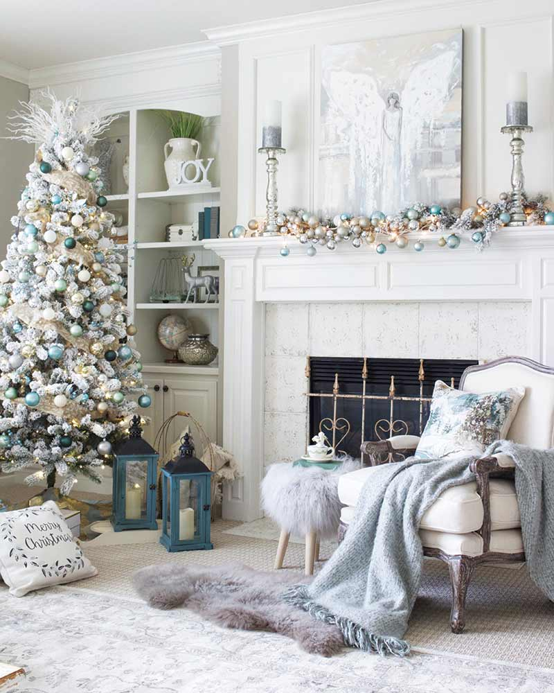 White and light blue Christmas decor in den with fireplace