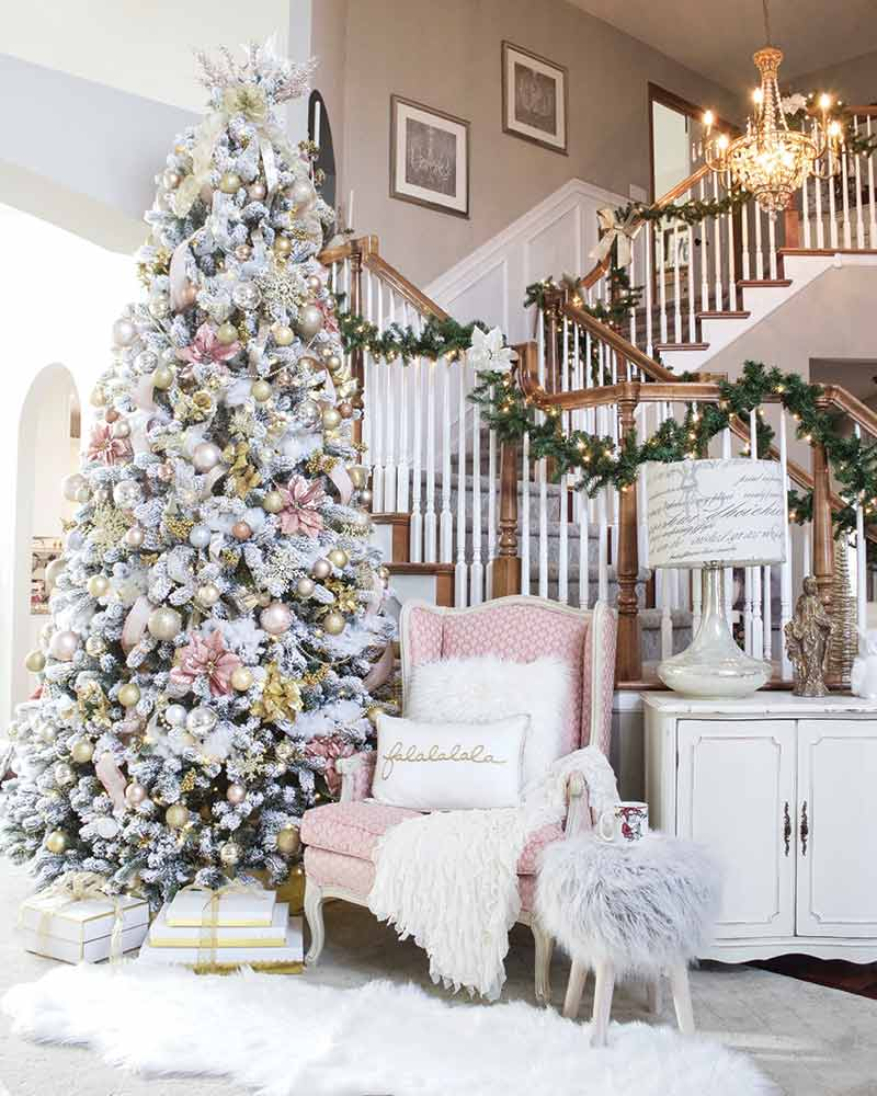 Grand stairwell with garland and pink accented Christmas tree