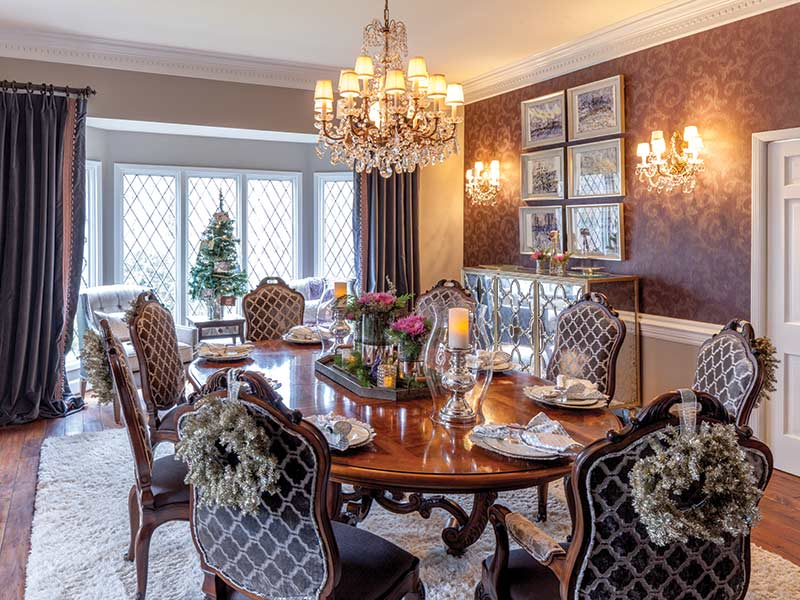 dining room with tinsel on the back of the chairs