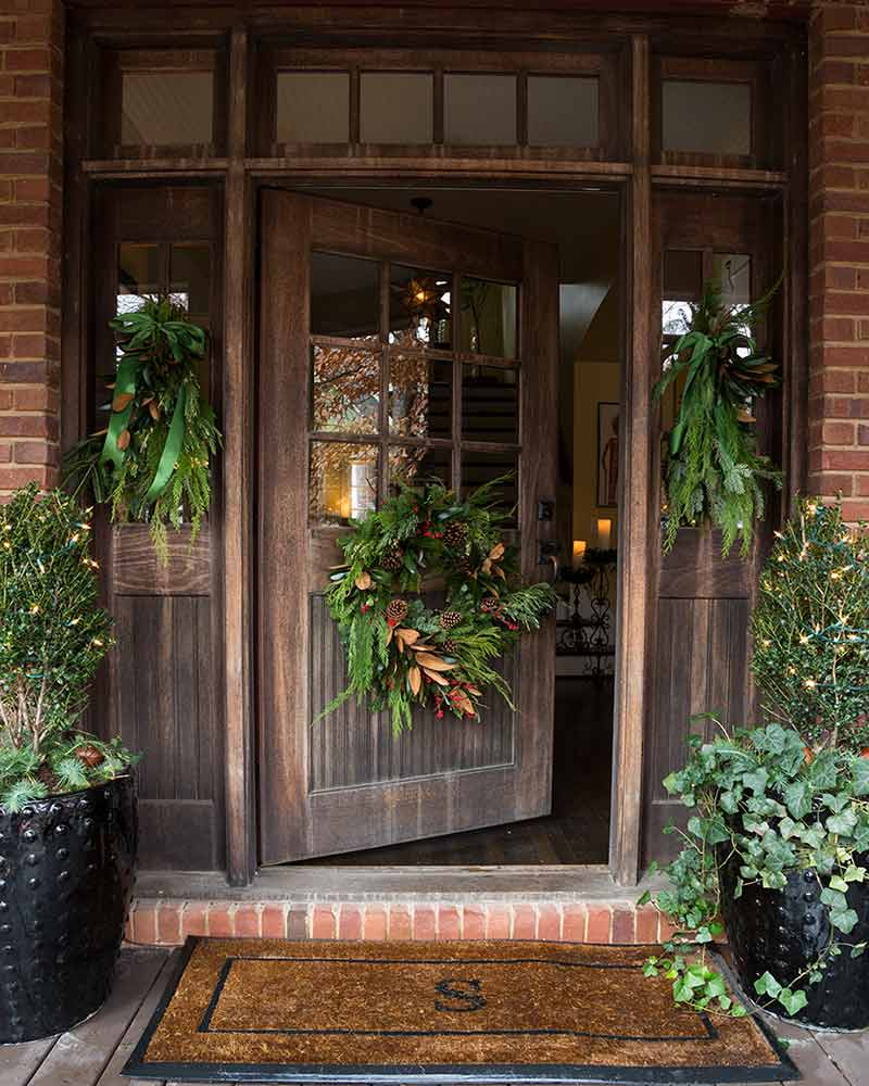 dark brown wooden front door with wreath
