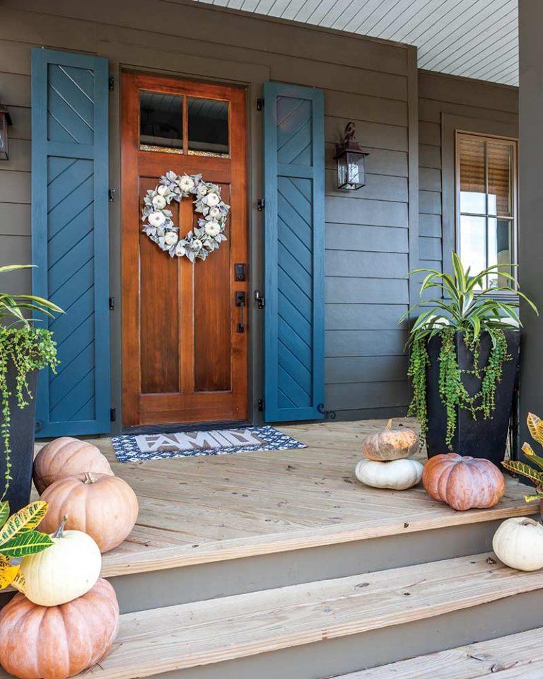 front door with blue shutters and pumpkins