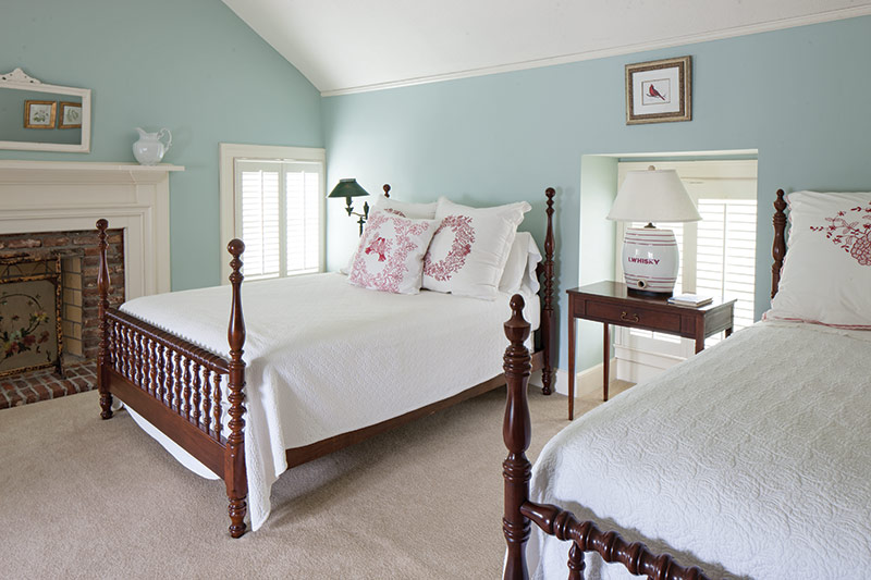 Guest suite with light blue walls and two full size beds