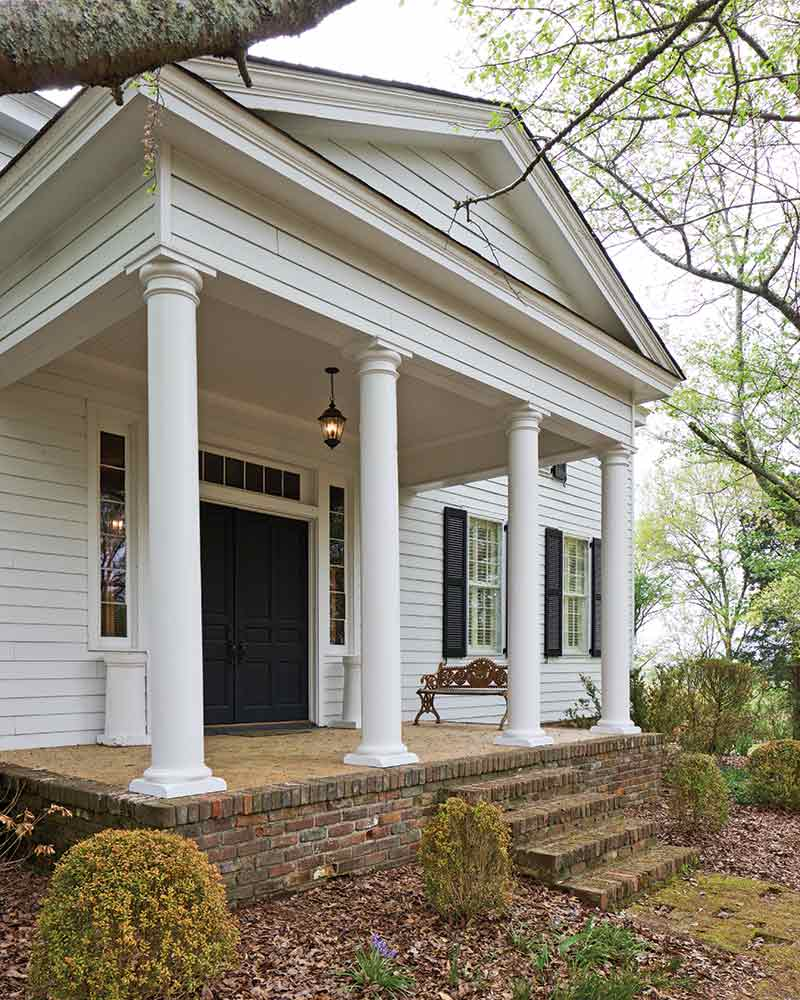 country home exterior - white columns and black front door