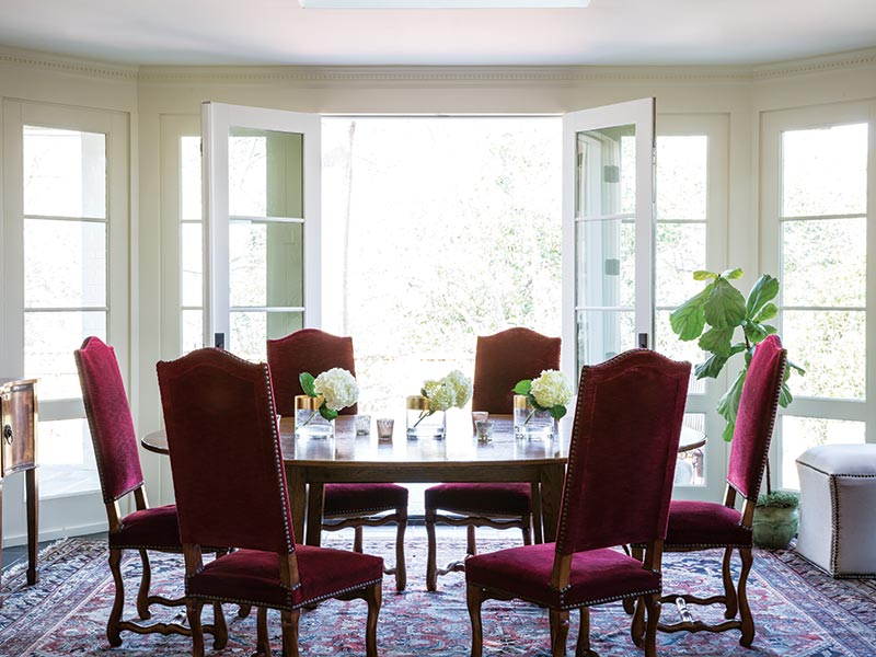 dining room with deep red velvet chairs and French doors