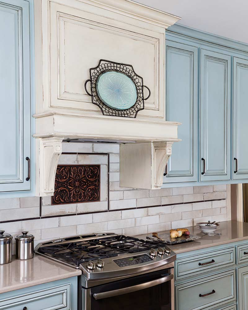 stove top, light blue cabinets, off-white subway tile backsplash