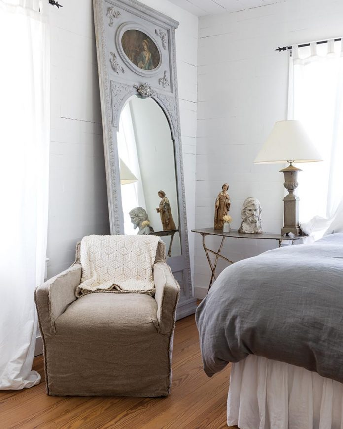 neutral bedroom with vintage mirror propped against wall