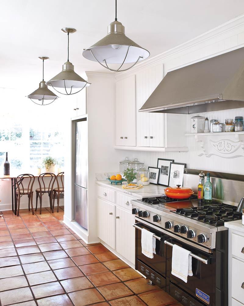 White minimalist kitchen with terra cotta tile floors