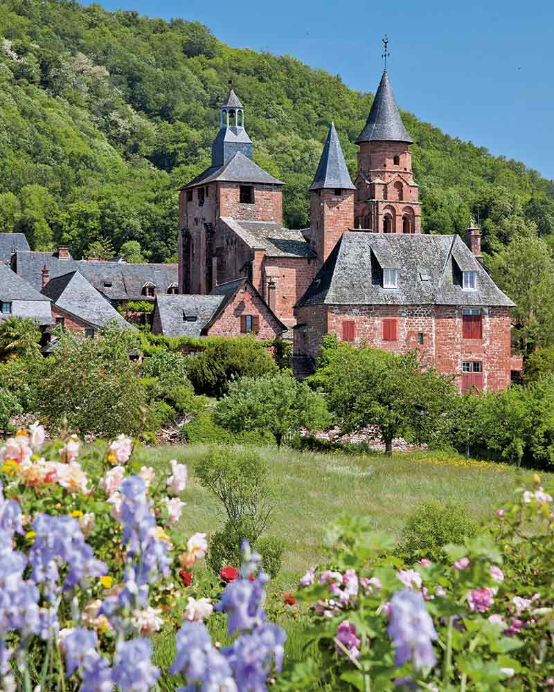 Collonges's dark red brick houses, roofed in blue-tinged lauzes, back onto the thickly wooded hillside.