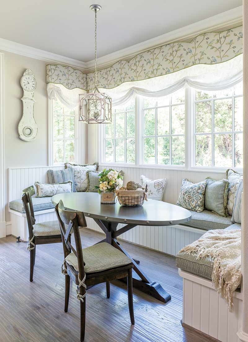 light-filled breakfast nook with booth seating and a soft color scheme