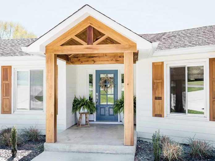 white exterior with light wood beams and blue front door